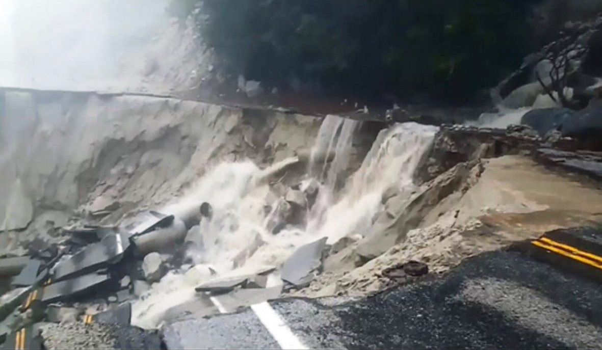 road collapsed due to slide with water pouring down rim