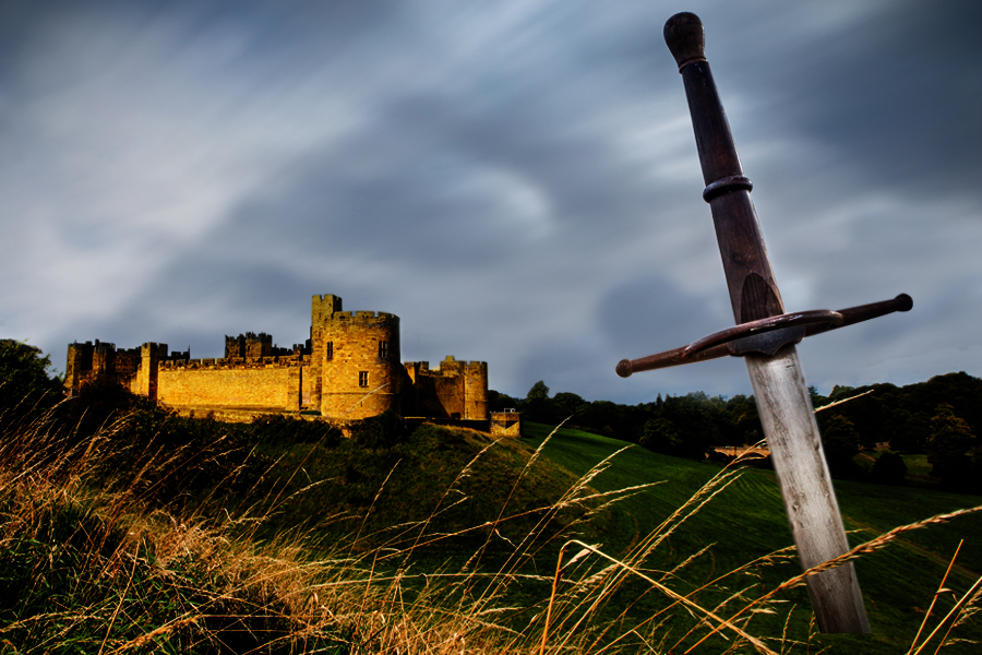 Sword stuck in the grass in front of a castle