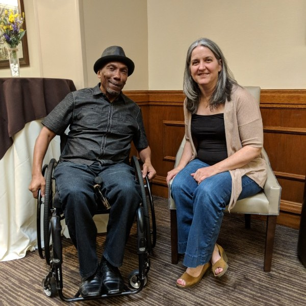 photo of council member martez williams, who is an african american gentleman who uses a wheelchair and is dressed in a nice black shirt and hat and jeans, sits next to T.H.D.A.'s Bettie Teasley, who is a white woman with jeans and a sweater - they are sitting in hotel lobby