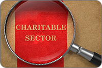 """photo: magnifying glass with words """"charitable sector"""" (iStockphoto)"""