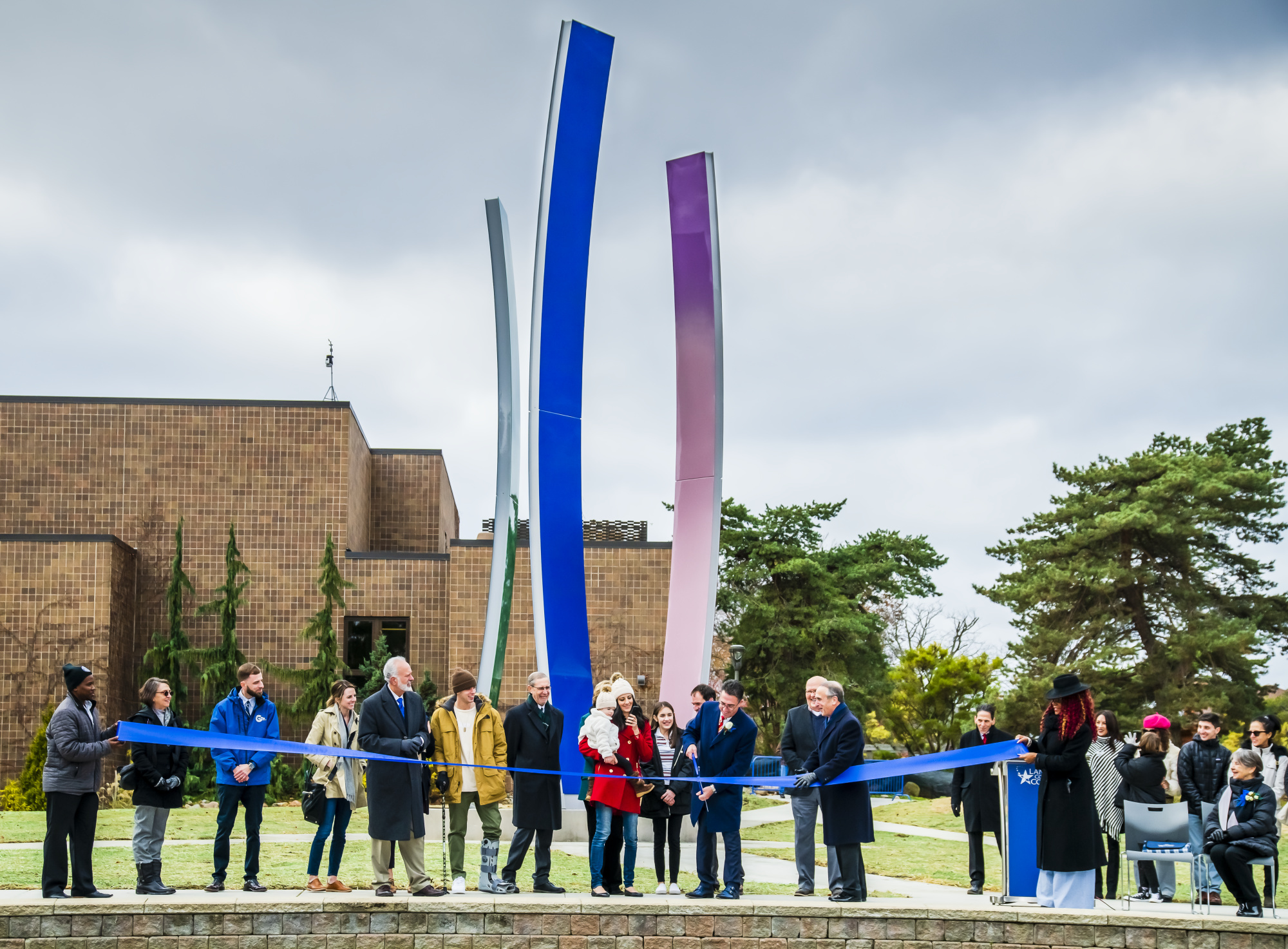 LCC Trustee Andrew Abood, surrounded by his family and other trustees, cuts the ribbon on the Upward Bound sculpture.