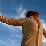 A man reaches to the sky with outstretched arms
