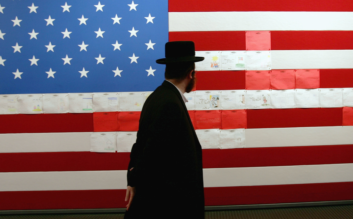A Jewish man stares at an artistic rendering of an American flag