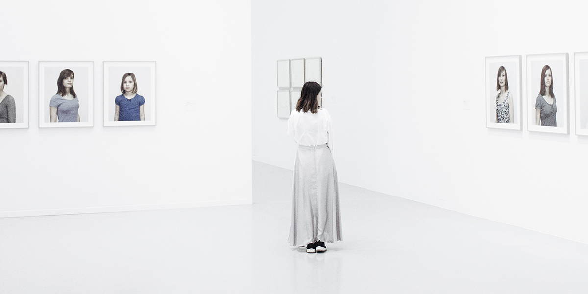Woman in a museum looks at portraits hanging on the wall.