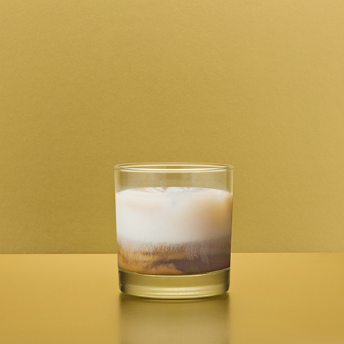 A white russian drink sits on a mustard yellow studio sweep.