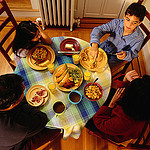 A family dines together at the dinner table.
