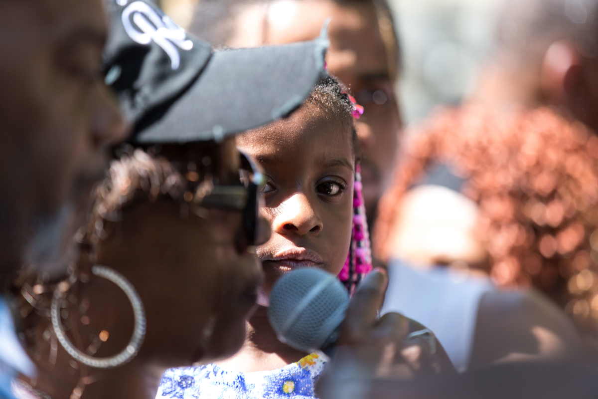 A young girl watches as her mother protests.