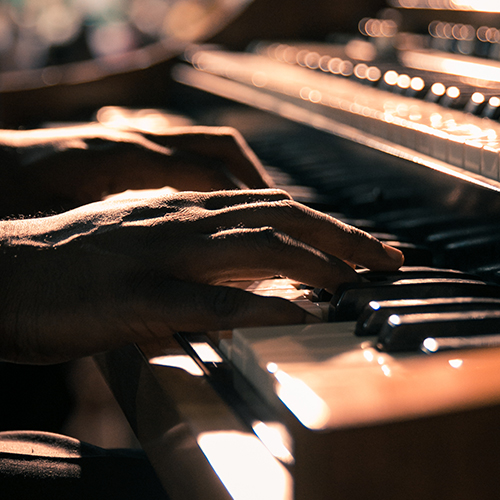 Hands play the piano in evening light.