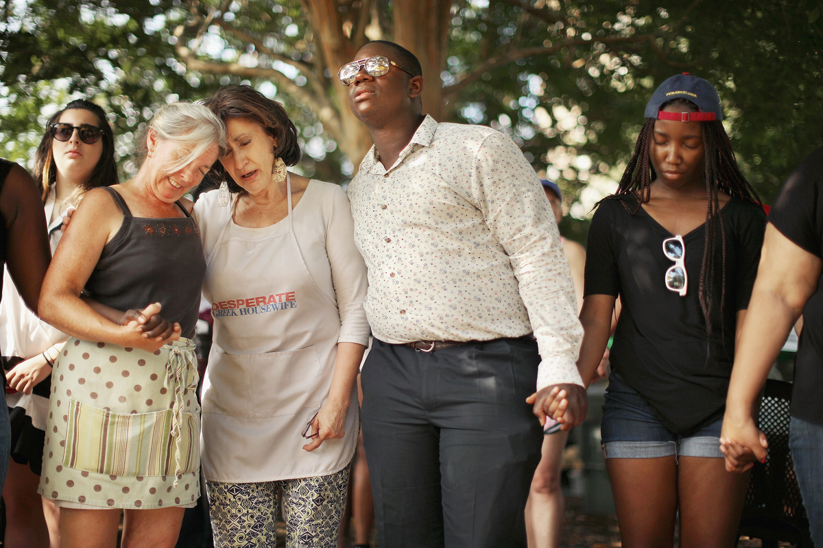 People hold hands and sing during a prayer service in Marion Square, two blocks from where nine people were shot to death Wednesday at Emanuel African Methodist Church June 20, 2015 in Charleston, South Carolina.