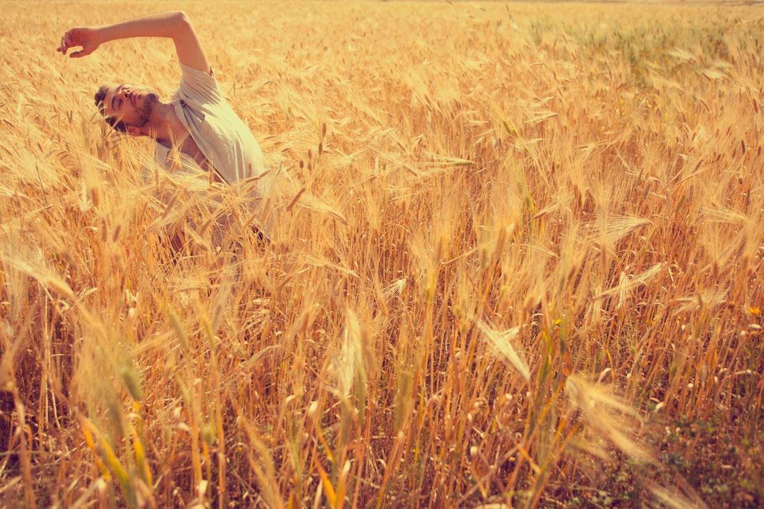 A man stretches in a field of wheat