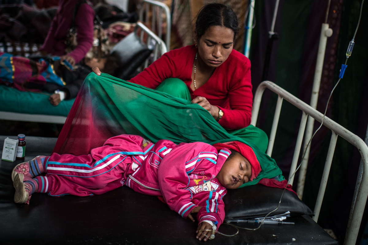 Sanjhana Tamang takes care of her daughter Simran Tamang, 3, as she lays in bed at a temporary hospital suffering from Typhoid fever after the earthquake in Shanku on April 30, 2015 in Kathmandu, Nepal. Photo by David Ramos.