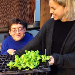 Noah and his aide examining aquaponic lettuce.
