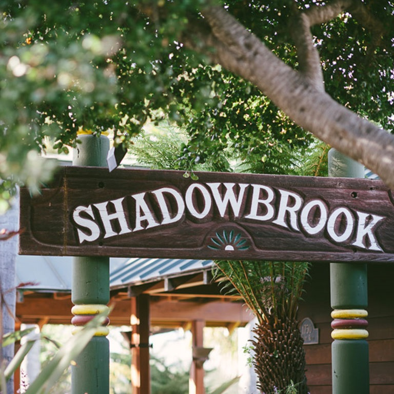 A view of the Shadowbrook sign with beautiful trees and plants.