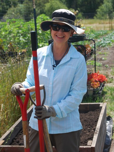 A volunteer takes a break from work in the garden to pose with tools.