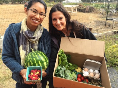 Volunteer holding produce and eggs for the farm stand.