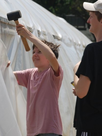 A young volunteer helps construct the greenhouse.