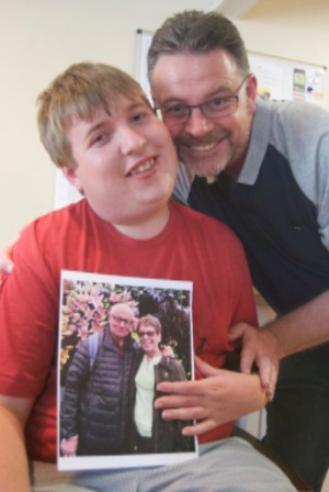 Scottie Goodwin with his father Mark and a picture of his grandparents, Mark's parents, Eddie and Sue.