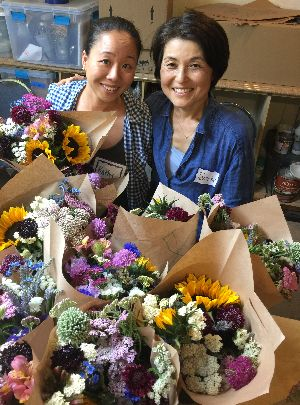 Kathy and Tomoko sit smiling behind many beautiful bouquets.