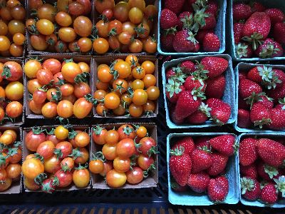 Yellow cherry tomatoes and strawberries in boxes.