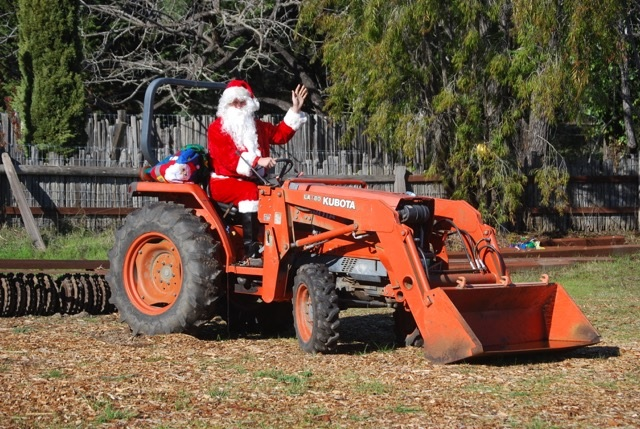 A volunteer in a Santa suit with presents driving a tractor on the farm.