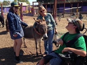 Tessa and Vicki pet a burro while Noah smiles.