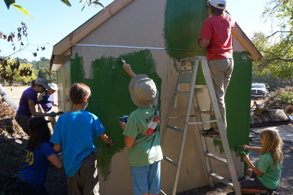 Volunteers young and older work together to paint the shed.