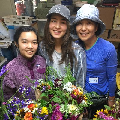 Volunteers pose with floral bouquets,