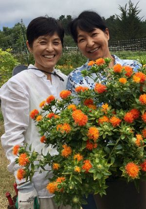Tomoko and Norie holding cut flowers that they will use in bouquets, table arrangements, or craft items.