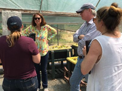 Natalie Markovics describes her work in the greenhouse to the Cabrillo visitors.
