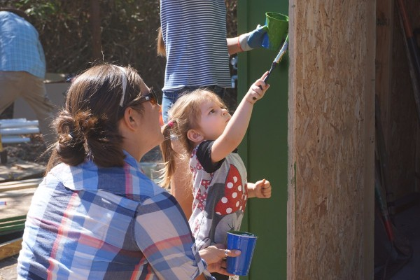 One of the youngest volunteers and her mother paint the shed.