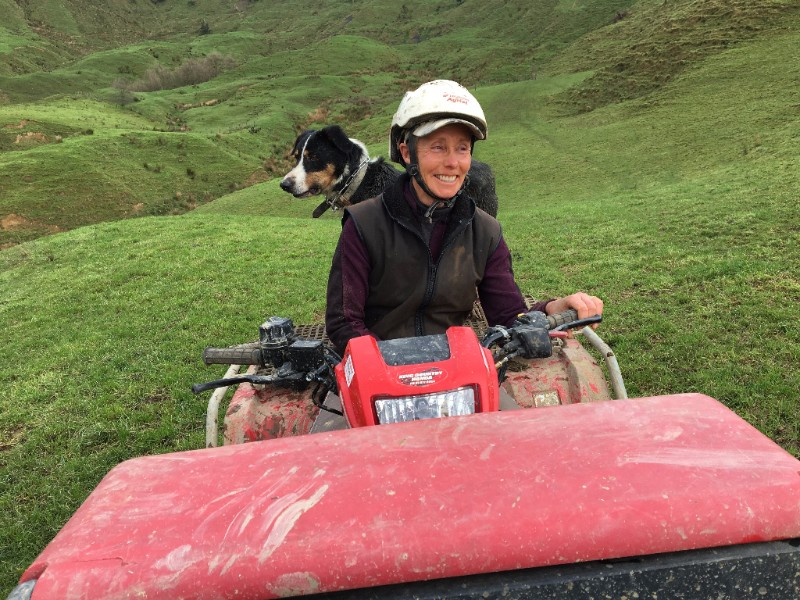 Sheep and beef farmer Wendy Coup and dog on the farm quad bike.