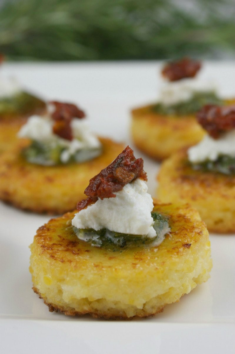Polenta Cakes topped with pesto, cheese, and tomatoes