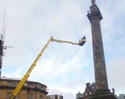 Cherrypicker reaching to statue