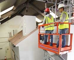 Two workers training on scissor lift indoors