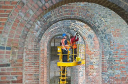 Workers checking arches using cherrypicker