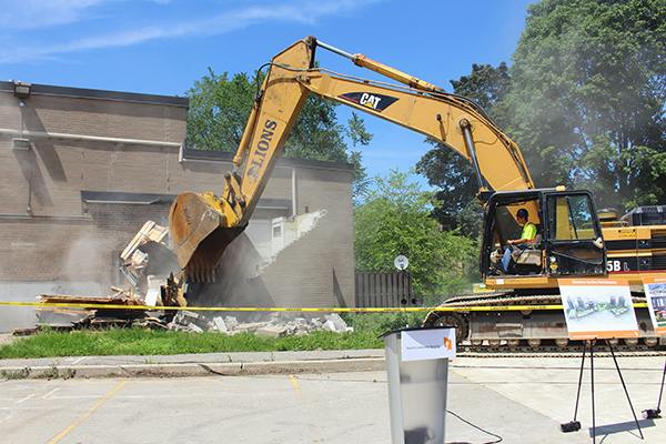 Large construction machine tearing down aging townhouses at Allenbury Gardens.