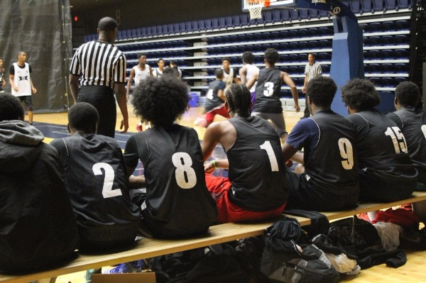 Youth from the Midnight Madness Program watching the basketball game from the sidelines.