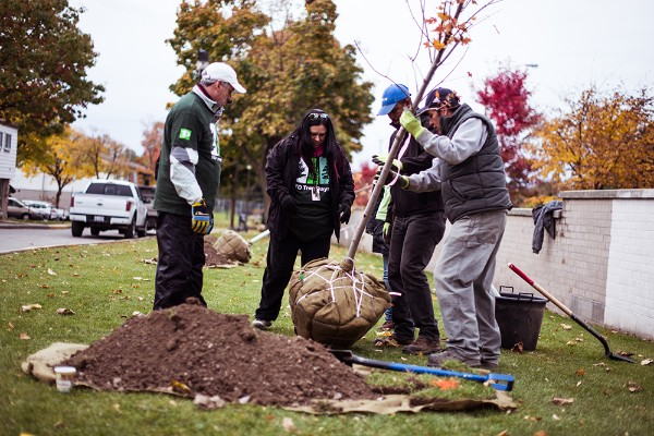 Volunteers work together to plant new a new tree in the Chester Le Community.