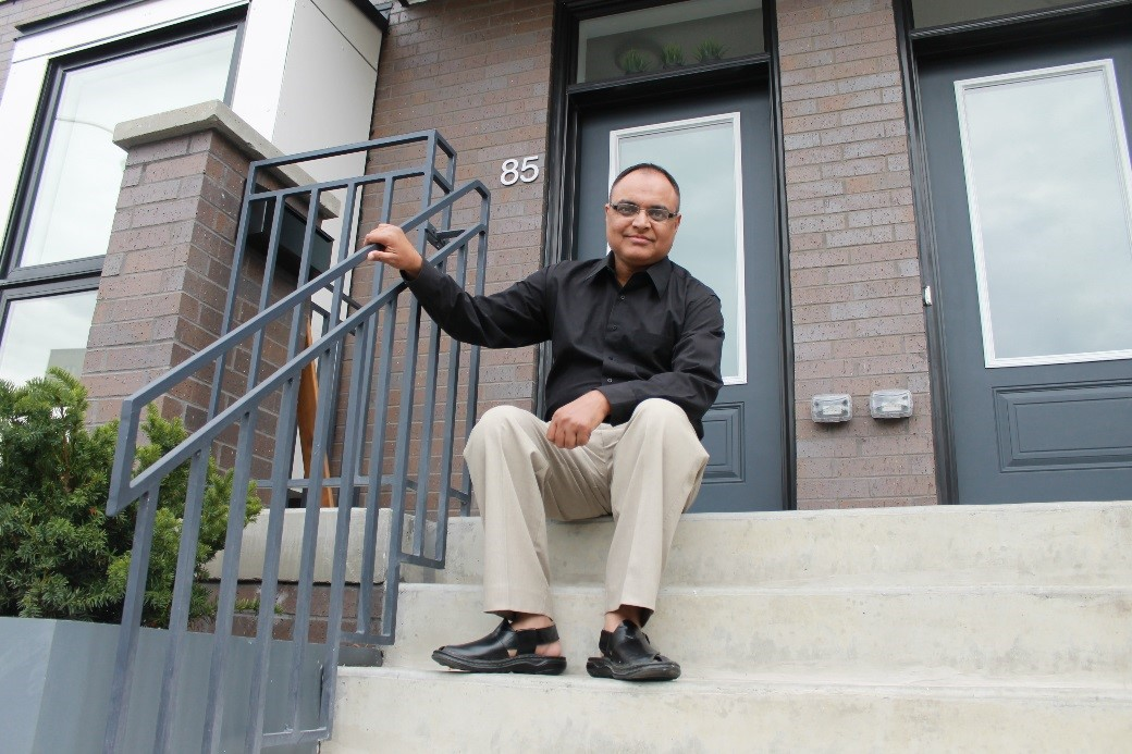 Alexandra Park resident Waseem Tahir sits on the stairsteps of his new townhome.