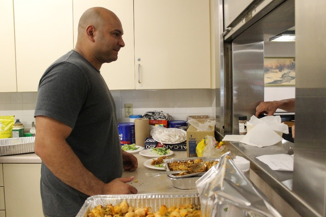 A volunteer serving food to Toronto Community Housing residents in Scarborough.