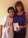 Helen Scarr with son Jaden holding plaque