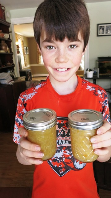 Young boy holding 2 jars of marmalade