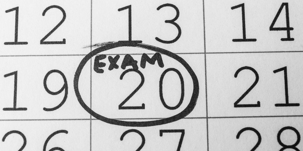 Overhead shot of a calendar with a date circled with the word Exam written above it.