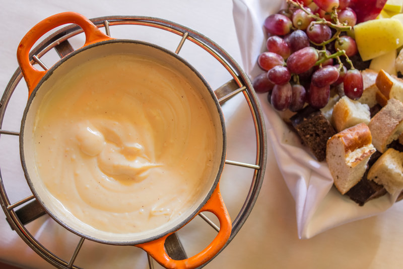 cheese fondue in pot with grapes