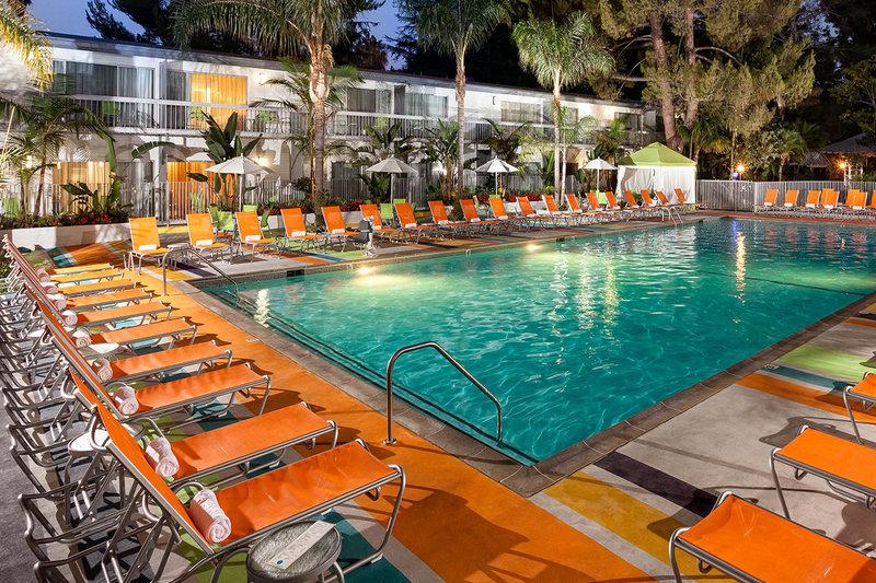 orange reclining chairs surrounding pool