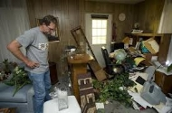 man looks at earthquake damage in his living room