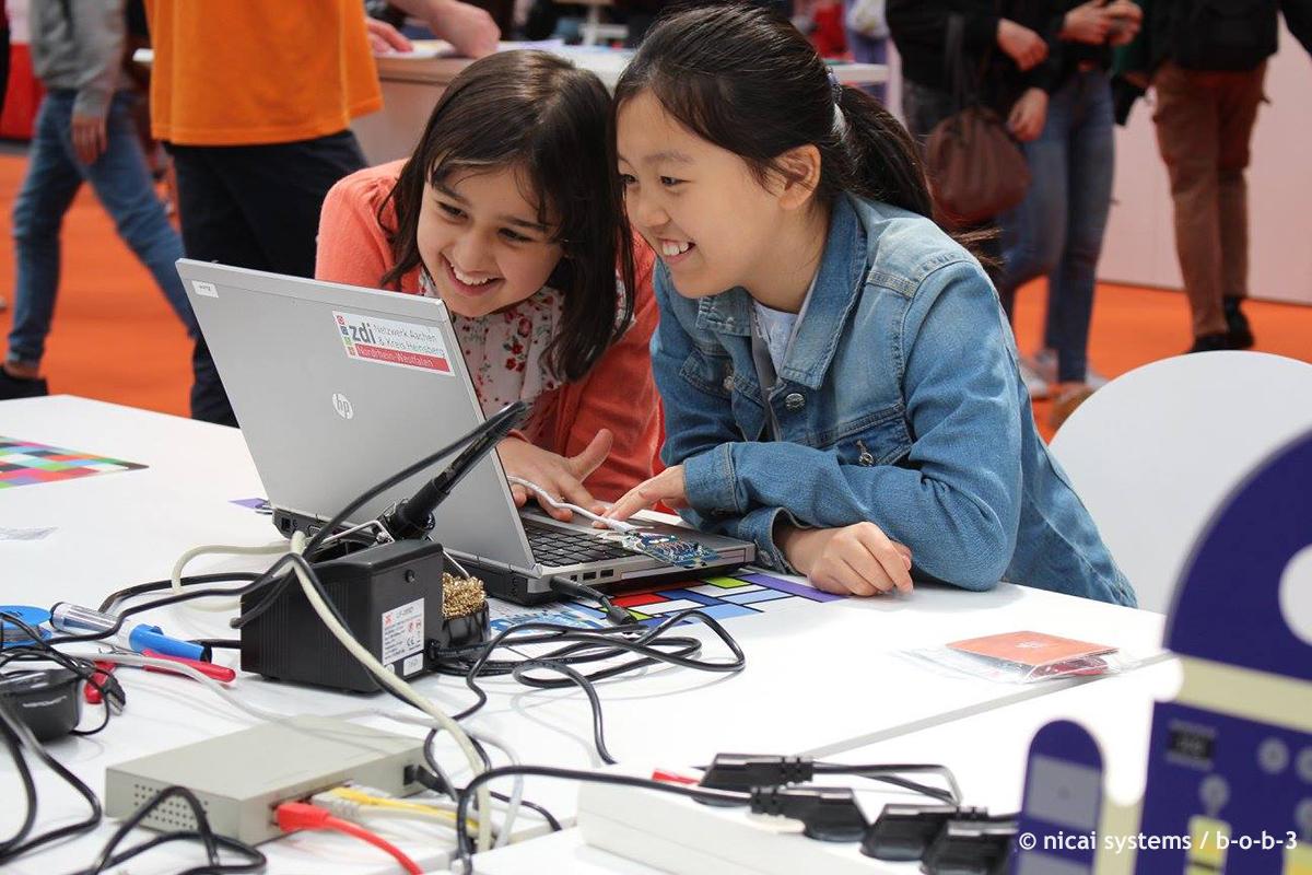Zwei Mädchen lernen auf der IdeenExpo mit dem Roboter B-O-B-3 Programmieren. © nicai systems / b-o-b-3