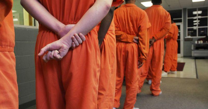 Inmates in orange jumpsuits line up.