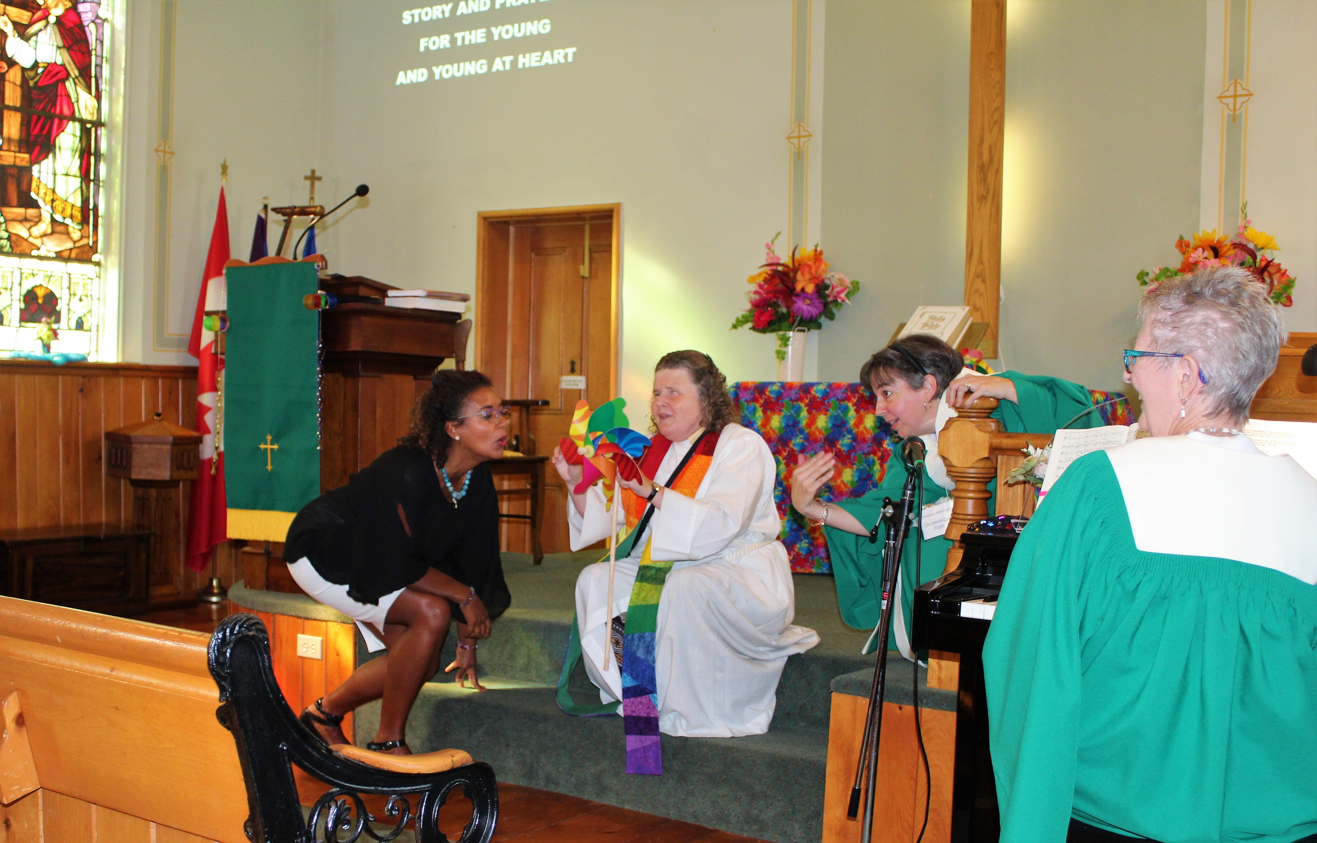 Front of a church; minister holds a windmill while woman to her left blows on it, woman to right encourages, and pianist looks on laughing.