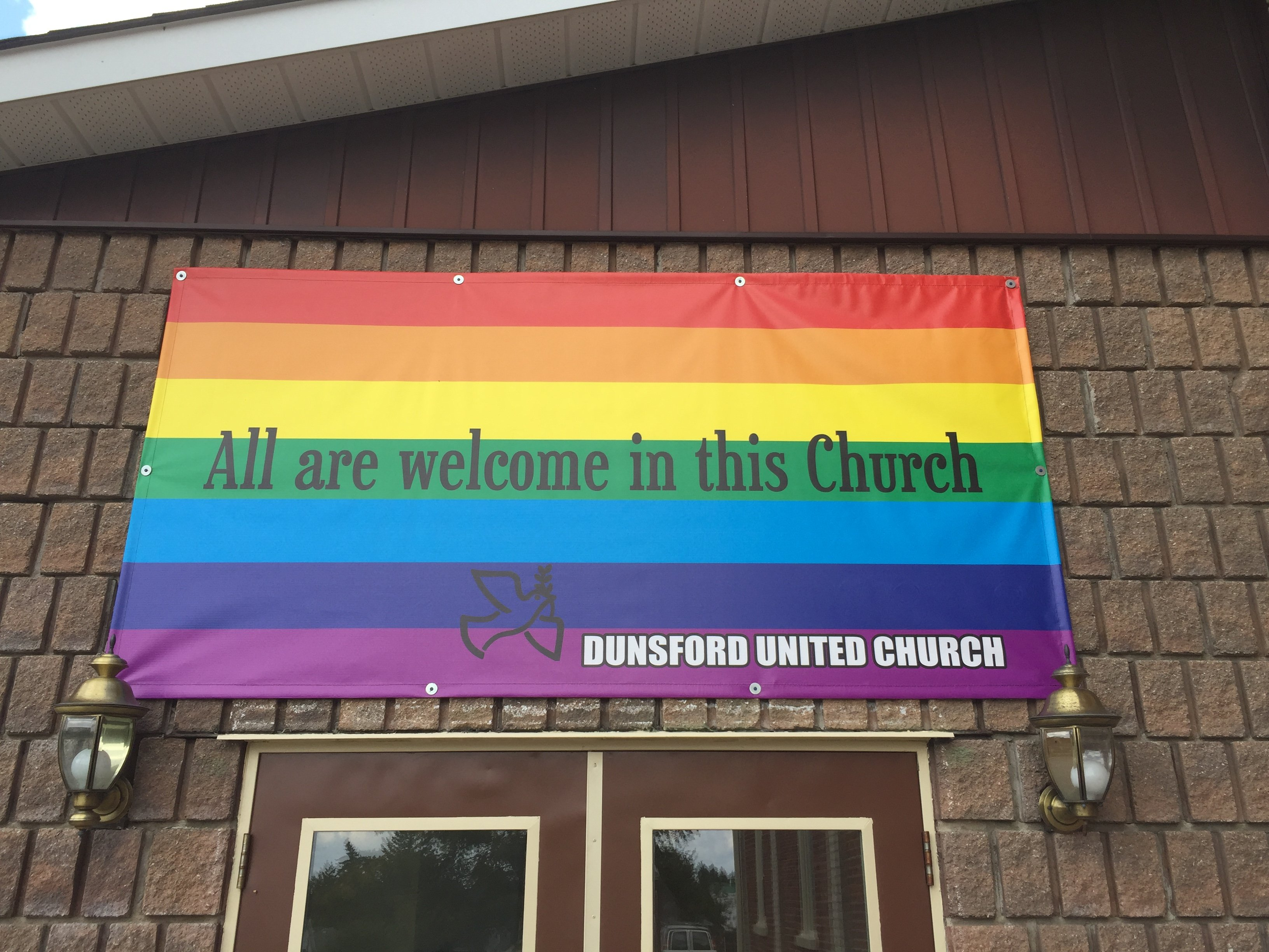 """Dunsford United Church rainbow banner reading """"All Are Welcome in this Church""""."""